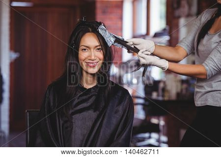 Hairdresser dyeing hair of her client at a salon