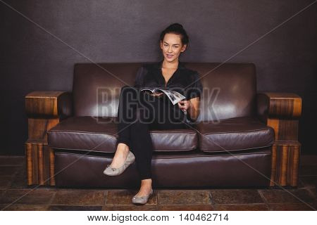 Portrait of smiling woman sitting on sofa and reading a magazine at the hair salon