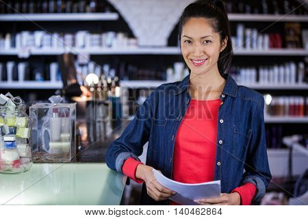 Portrait of smiling female hairdresser holding a form at the hair salon