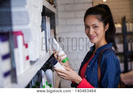 Portrait of smiling female hair dresser selecting shampoo from shelf at a salon