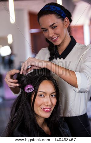 Portrait of female hairdresser styling customers hair at a salon