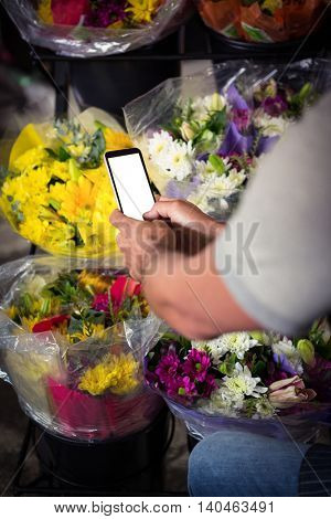 Mid section of male florist taking photo of flower bouquet on mobile phone at his flower shop