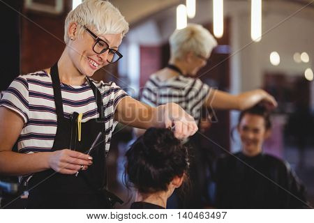 Smiling female getting her hair trimmed at a salon