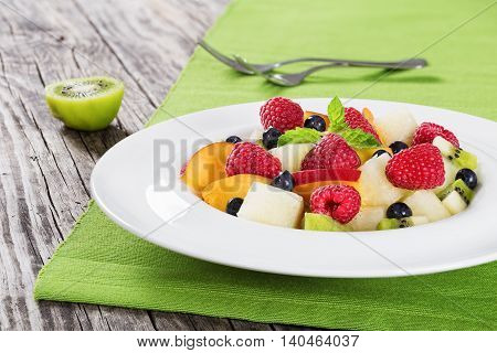 delicious fruit and berry summer salad decorated with mint leaves in white wide rim dish on wooden boards close up