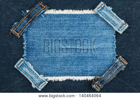 Frame with two straps jeans lies on the blue denim with space for your text
