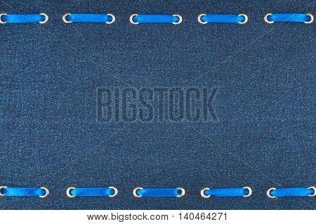 Fashionable beautiful background blue satin ribbon inserted in denim fabric with space for your creativity
