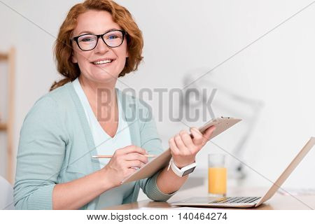 Full of joy. Cheerful beautiful senior woman holding folder and working while sitting at the table