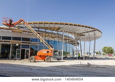 Zrenjanin Vojvodina Serbia - September 14 2015: High elevated cherry picker people are working at new assembled canopies on construction site.