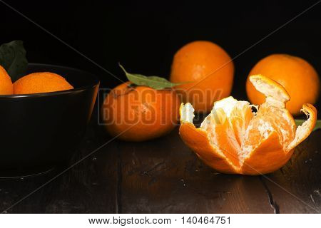 Tangerines with leaves on old dark wooden table. Christmas concept. Vintage style. Selective focus