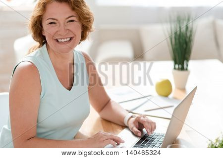 Can not hide my emotions. Pleasant delighted overjoyed woman smiling and sitting at the table while using laptop