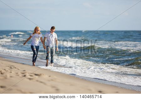 Cheerful couple are walking on the beach summer time