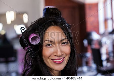 Portrait of smiling woman sitting with hair rollers at a salon