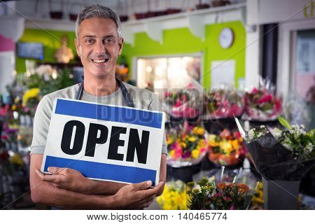Portrait of male florist holding open signboard at his flower shop