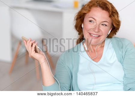 Good way to relieve stress . Pleasant delighted smiling senior woman holding cell phone and listening to music while resting