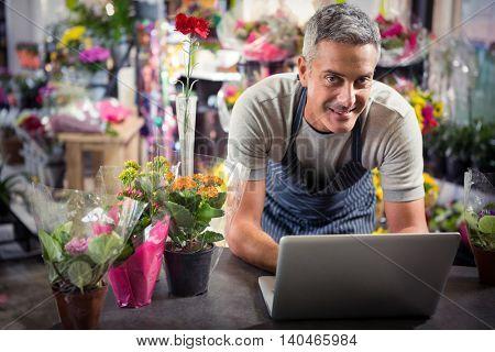 Happy male florist using laptop at his flower shop