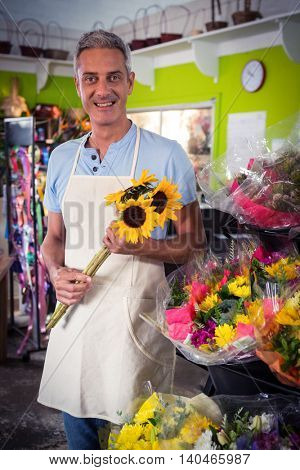 Portrait of happy male florist holding bunch of yellow sunflower at his flower shop