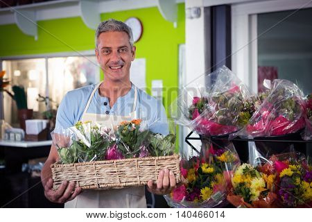 Portrait of male florist carrying plant pot in wicker basket at his flower shop