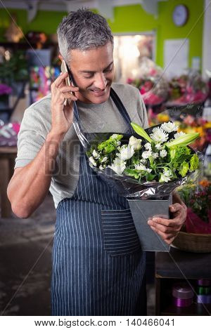Male florist holding bunch of white flower while talking on mobile phone at his shop