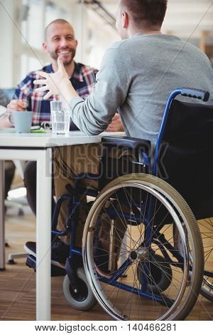 Happy handicap businessman discussing with colleague in creative office