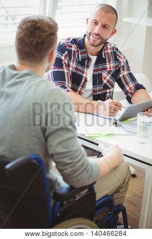 Young businessman using digital tablet while discussing with handicap colleague in creative office