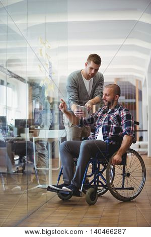 Handicap businessman discussing with colleague while sticking adhesive notes on glass window in creative office