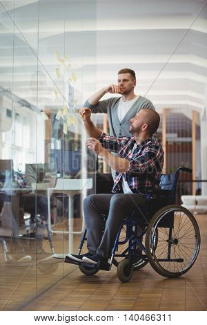 Handicap businessman and colleague sticking adhesive notes on glass window in creative office