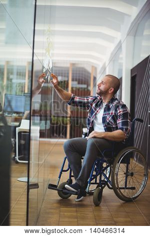 Handicap businessman sticking adhesive notes on glass window in creative office