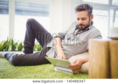 Businessman working on laptop while reclining in creative office