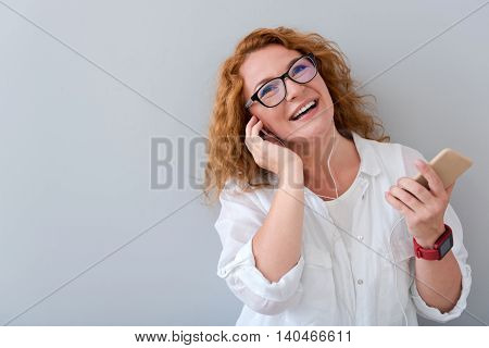 Just relax. Overjoyed smiling beautiful woman wearing headphones and holding cell phone while listening to music