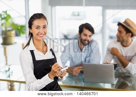 Portrait of smiling waitress taking an order in cafe