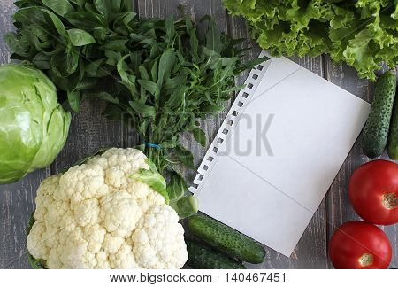 Paper leaf and composition of vegetables on grey wooden desk. Tomato, cucumber, cabbage, cauliflower, basil, arugula. Top view. Modern photography. The best for recipies.