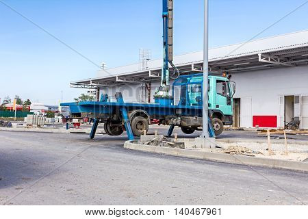 Truck with elevated bucket has lateral stabilizer extended to make better stability.