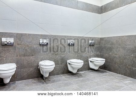 Modern designed of public toilet bowls lined up no privacy.