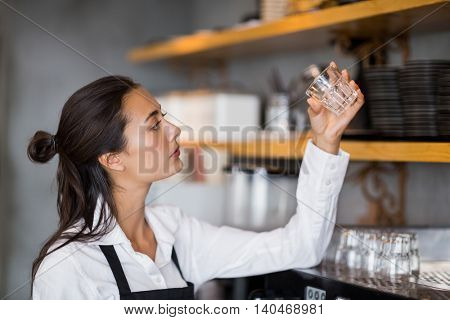 Waitress checking small glass in cafe