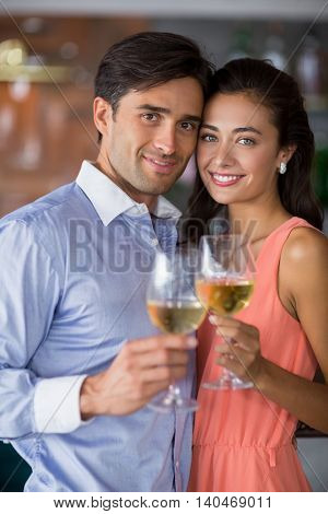 Portrait of young couple holding glass of wine in restaurant