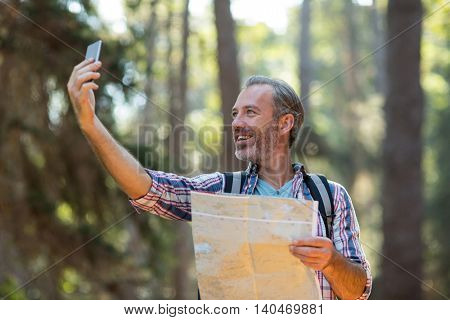 Happy hiker with map taking a selfie in forest