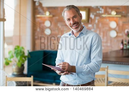 Portrait of smiling man writing in a file in restaurant