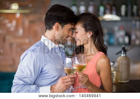 Romantic young couple toasting wine glasses in restaurant