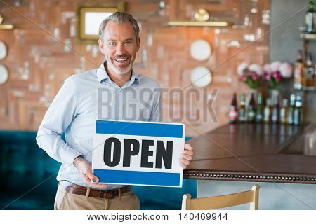 Portrait of man showing signboard with open sign in restaurant