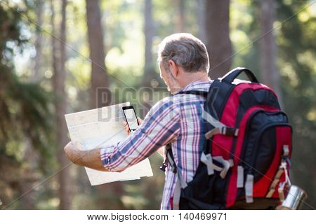 Hiker with backpack using mobile phone and map in forest