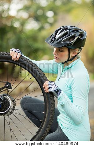 Fit woman repairing bicycle tyre in countryside