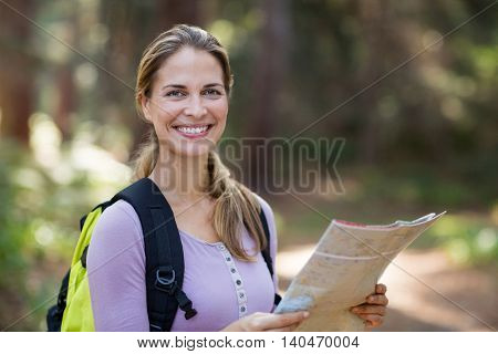Portrait of smiling woman standing with map in forest