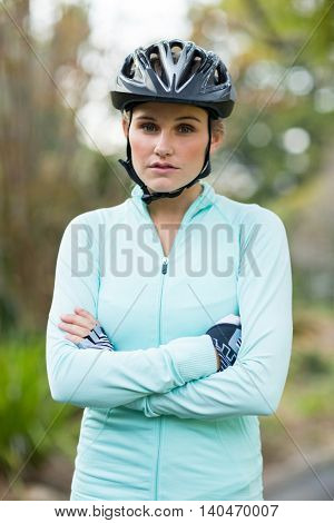 Female athletic in bicycle helmet standing with arms crossed