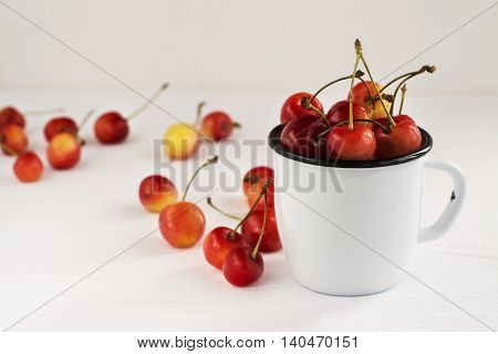 Sweet cherries in retro enamel mug over white background. Summer harvest. Natural light. Selective focus