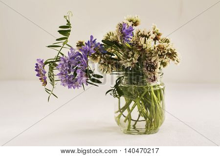 Summer bouquet of wild field flowers over white background. Natural light, Selective focus