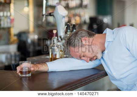 Unconscious businessman holding whiskey glass lying on a counter in restaurant