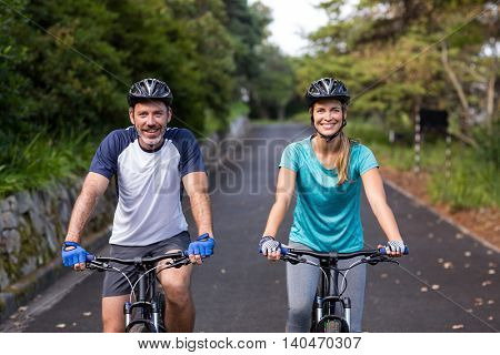 Smiling athletic couple cycling on the open road