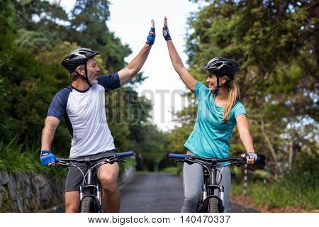 Happy athletic couple giving high five while riding bicycle on the road
