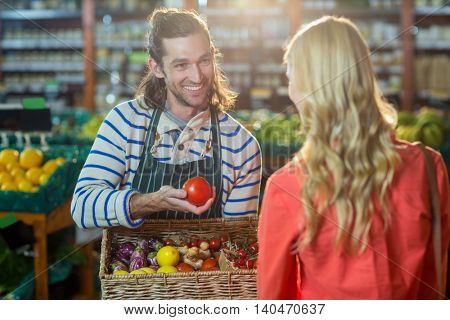 Male staff assisting woman in selecting fresh vegetables in supermarket