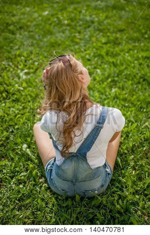 girl sitting on the grass bent in sadness